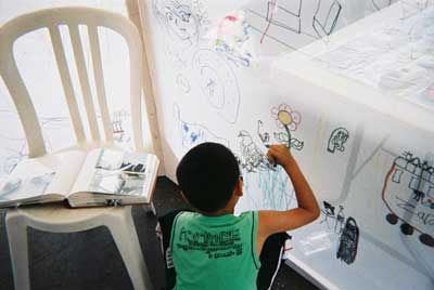 Back view of a young boy making a wonderful drawing of a pigeon near ground level in the drawing tent
