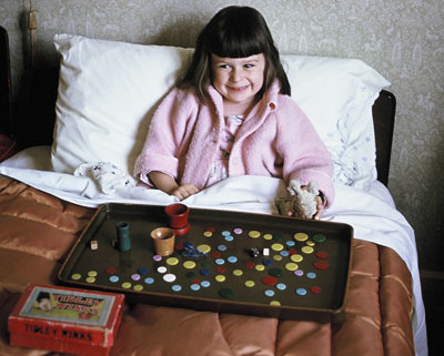Sally, aged about 4, sat up in bed with a tray of coloured tiddly winks.