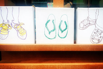 3 small canvases of feet outside the gallery